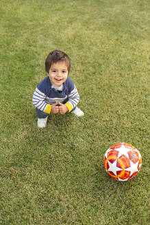 Portrait of happy little boy with a ball crouching on lawn - VGF00317