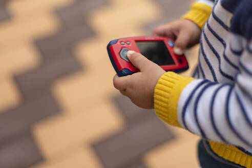 Hands of little boy holding toy mobile phone, close-up - VGF00323