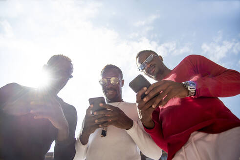 Three cool young men using cell phones in backlight - CJMF00152