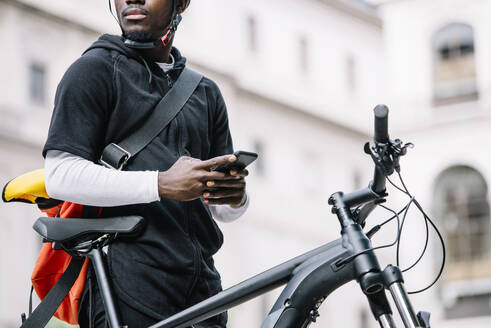Stylish young man with bicycle, smartphone and messenger bag in the city - CJMF00161