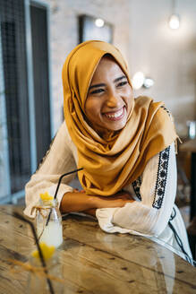 Young muslim woman wearing yellow hijab in a cafe - MPPF00208