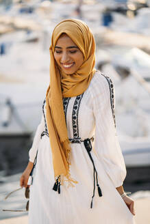 Young muslim woman wearing yellow hijab walking at the harbour - MPPF00211