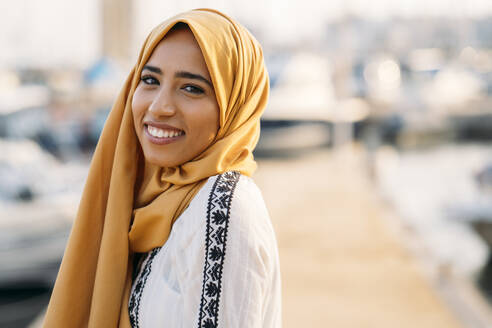 Young muslim woman wearing yellow hijab walking at the harbour - MPPF00217