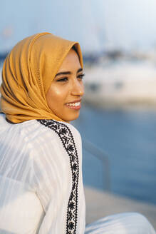Young muslim woman wearing yellow hijab at harbour - MPPF00220