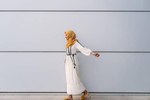 Young muslim woman wearing yellow hijab and walking in front of a white wall - MPPF00226