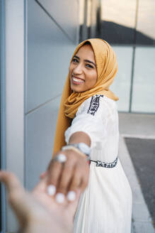 Young muslim woman smiling and taking hand of a man wearing hijab - MPPF00241