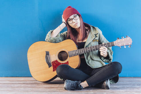 Teenage girl with guitar sitting on wooden floor - DLTSF00273