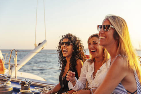 Friends laughing during boat trip in the evening light - MOSF00112