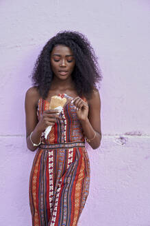Portrait of young woman enjoying ice cream in front of purple wall - VEGF00781