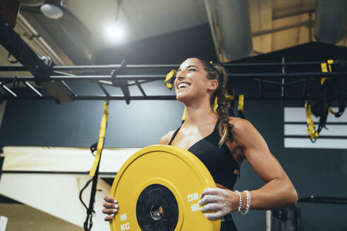 Smiling woman exercising with a weight in a gym - JCMF00260