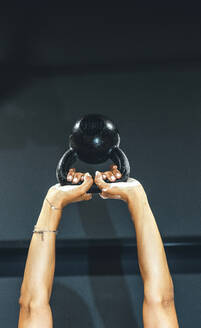 Arms of a woman exercising with a kettlebell - JCMF00275