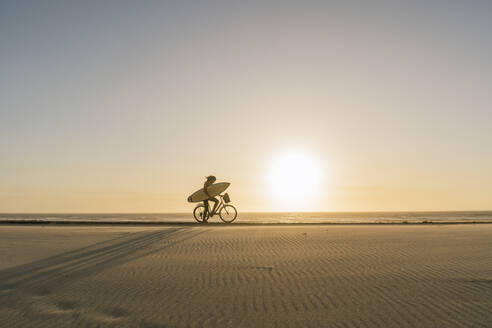 Surfer riding a bicycle during the sunset in the beach, Costa Nova, Portugal - AHSF01044