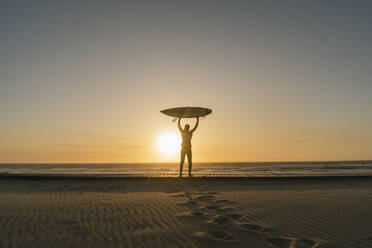 Surfer holding up surfboard on the beach, looking at sunset - AHSF01050