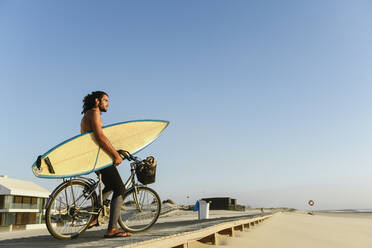 Surfer riding a bicycle during the sunset, holding surf board - AHSF01056
