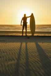 Surfer standing with the surfboard facing the sunset at the beach - AHSF01059