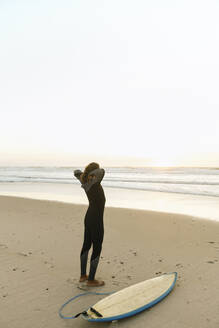 Portugal, Costa Nova, Surfer put on neoprene standing at the beach - AHSF01062