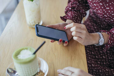 Woman holding smartphone in a cafe - MOMF00773