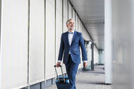 Mature businessman in a passageway with rolling suitcase on the go - DIGF08515