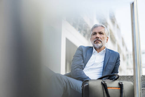 Mature businessman sitting on stairs in the city looking around - DIGF08536