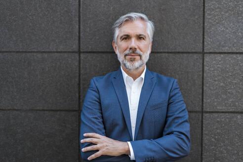 Portrait of confident mature businessman at a wall - DIGF08545
