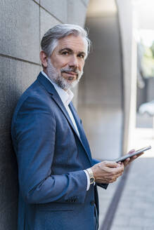 Portrait of confident mature businessman at a wall holding tablet - DIGF08551