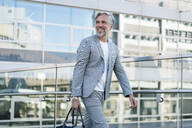Smiling fashionable mature businessman with bag on the go - DIGF08557