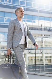 Fashionable mature businessman with travelling bag on the go - DIGF08566