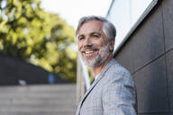 Portait of smiling fashionable mature businessman outdoors - DIGF08575