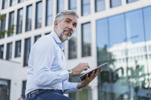 Mature businessman using tablet in the city - DIGF08581