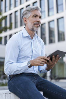 Mature businessman using tablet in the city - DIGF08587