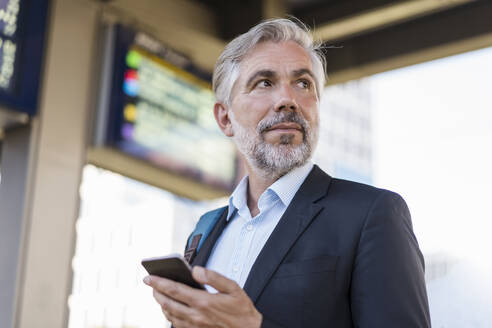 Portrait of mature businessman with cell phone at the station - DIGF08596
