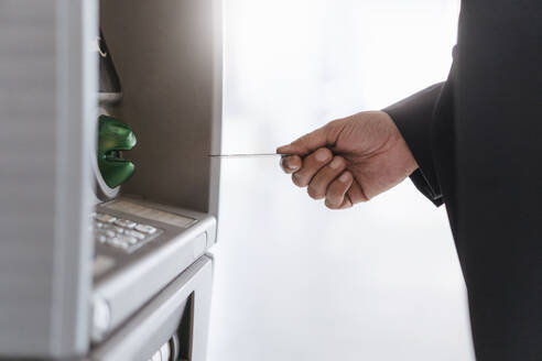 Close-up of businessman withdrawing money at an ATM - DIGF08599