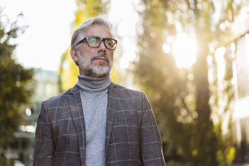 Portrait of fashionable mature businessman with glasses outdoors - DIGF08602