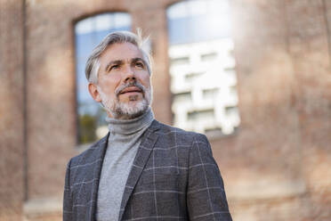 Portrait of fashionable mature businessman at a brick building - DIGF08611