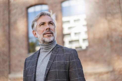 Portrait of fashionable mature businessman at a brick building - DIGF08611