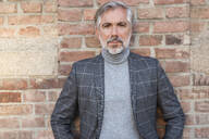 Portrait of fashionable mature businessman at a brick wall - DIGF08626