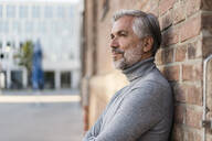 Portrait of mature businessman leaning at a brick wall - DIGF08629