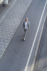 Top view of mature businessman walking on a road - DIGF08632