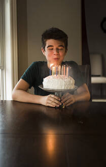 Teen boy blowing out the candles on his birthday cake at the table. - CAVF65892