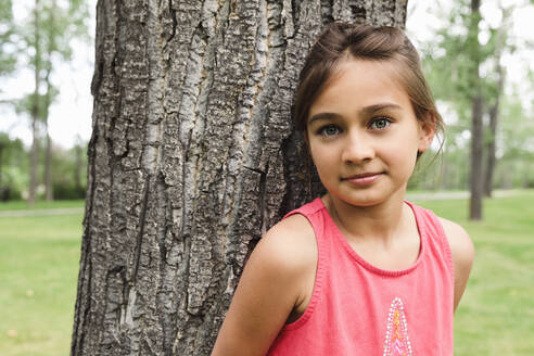 Portrait of young girl leaning against tree and looking at camera - HEROF39497