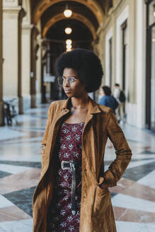 Young woman with afro hair in building corridor - CUF52562
