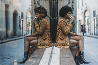 Young woman with afro hair having hot drink in front of cafe, Florence, Toscana, Italy - CUF52565