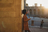 Young woman with afro hair using smartphone, leaning against stone wall, Florence, Toscana, Italy - CUF52571