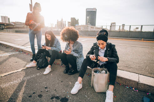 Friends sitting on kerb texting, Milan, Italy - CUF52733