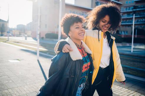 Two cool young female friends strolling on sunlit urban sidewalk - CUF52778