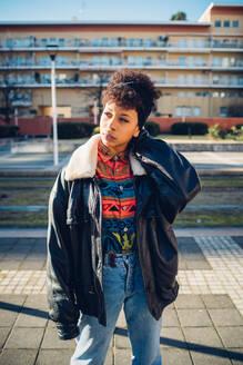 Cool young woman on urban sidewalk looking sideways, portrait - CUF52781