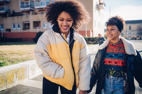 Two young female friends strolling on urban sidewalk - CUF52790