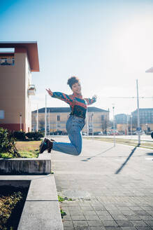 Young woman jumping from wall on urban sidewalk, full length portrait - CUF52793