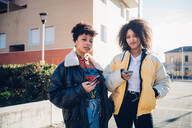 Two cool young female friends with smartphones on urban sidewalk, portrait - CUF52796