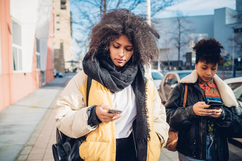 Two cool young women strolling and looking at smartphone on urban sidewalk - CUF52811